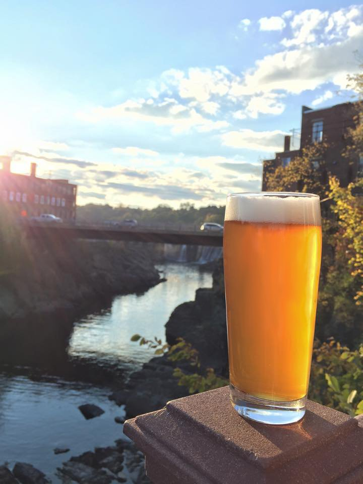 A glass of beer overlooking the Kennebec River from the deck of the Old Mill Pub in downtown Skowhegan.
