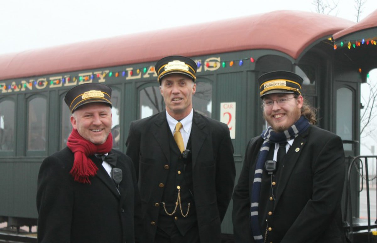 Conductor's help passengers find their car before departure.