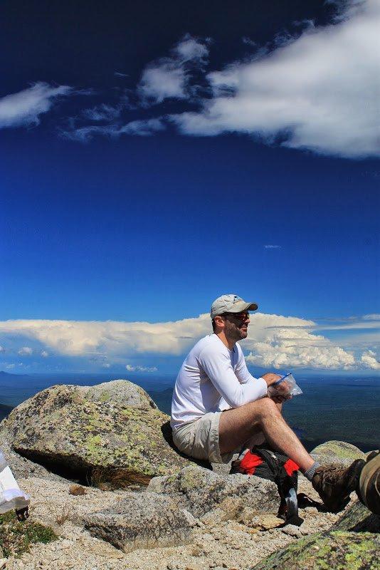Man sitting on rock atop Mount Katahdin.