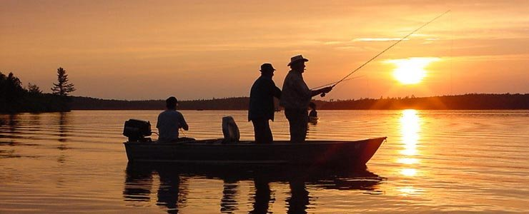 Two fisherman standing in their boat, fishing, at sunset.