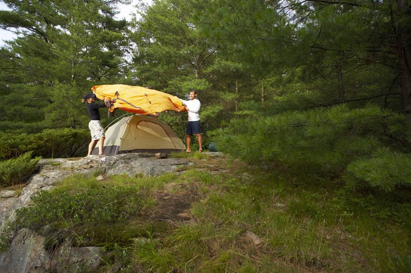 Setting up a tent out in the wilderness.