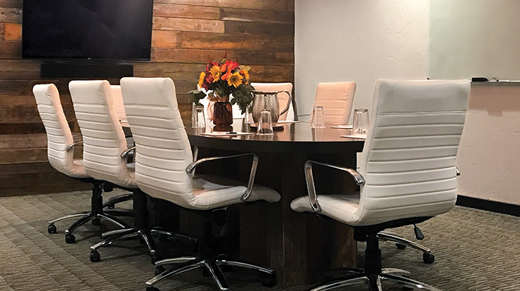 The executive boardroom is provides comfortable seating and includes a flatscreen TV, dry erase board, and wet bar.
