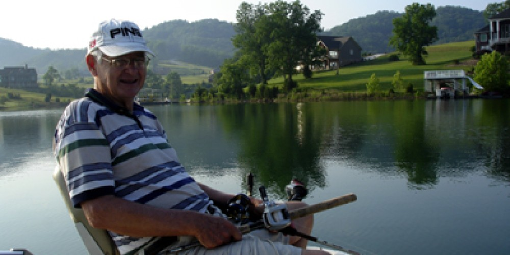 Serious fisherman with both rods and running trolling motor with foot – Elizabeth Weiss
