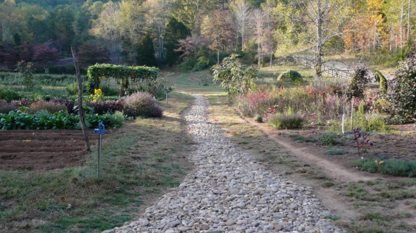 A view down the stone path along the property farm where vegetables and herbs are grown for use in the restaurants. – Kenny Markanich