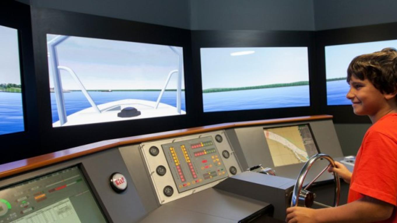 A student experiences life on the river through the simulator at the River Discovery Center.