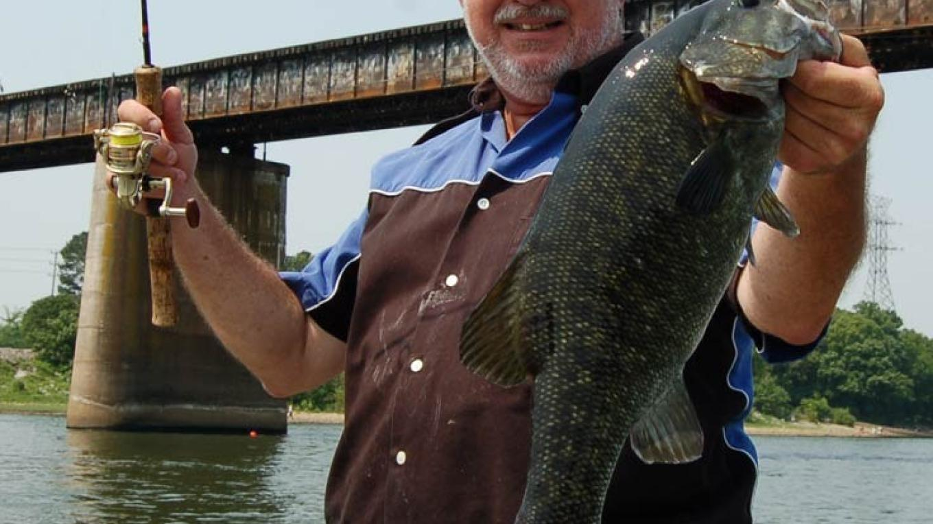 Richard Simms, The Guide, shows off a bragging-sized smallmouth bass. – John Sloan