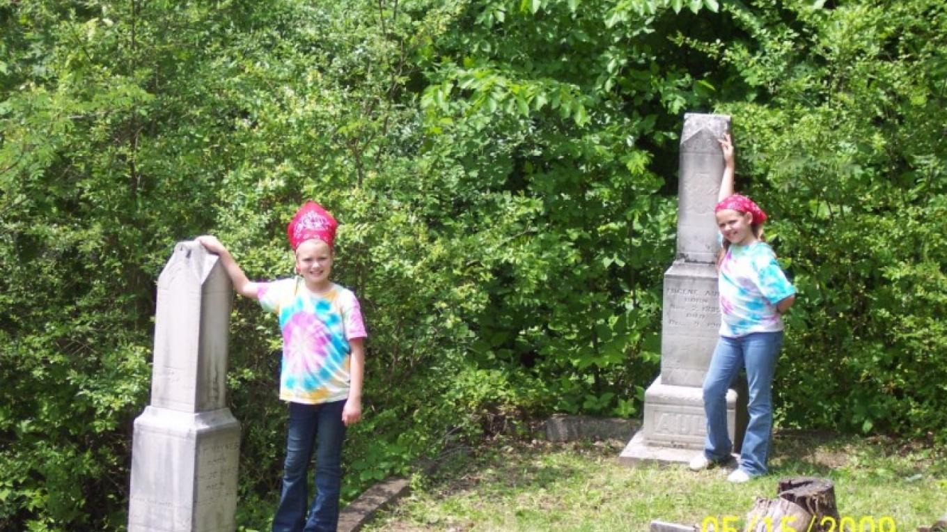 Students next to headstones of Coal Creek miners who perished in Cross Mountain Mine Disaster of 1911 at back of Briceville Cemetery – Coal Creek Watershed Foundation, Inc.