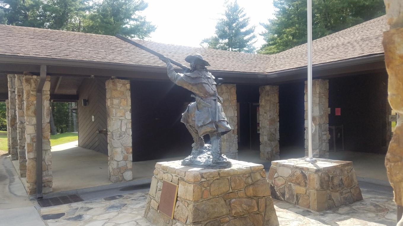 Sculpture of Overmountain patriot militiaman crouched ready to fire at Sycamore Shoals State Park in Tennessee. The banks of the Watauga River in present-day Elizabethton was the site of the militia muster prior to the Battle of Kings Mountain. – Mark Engler