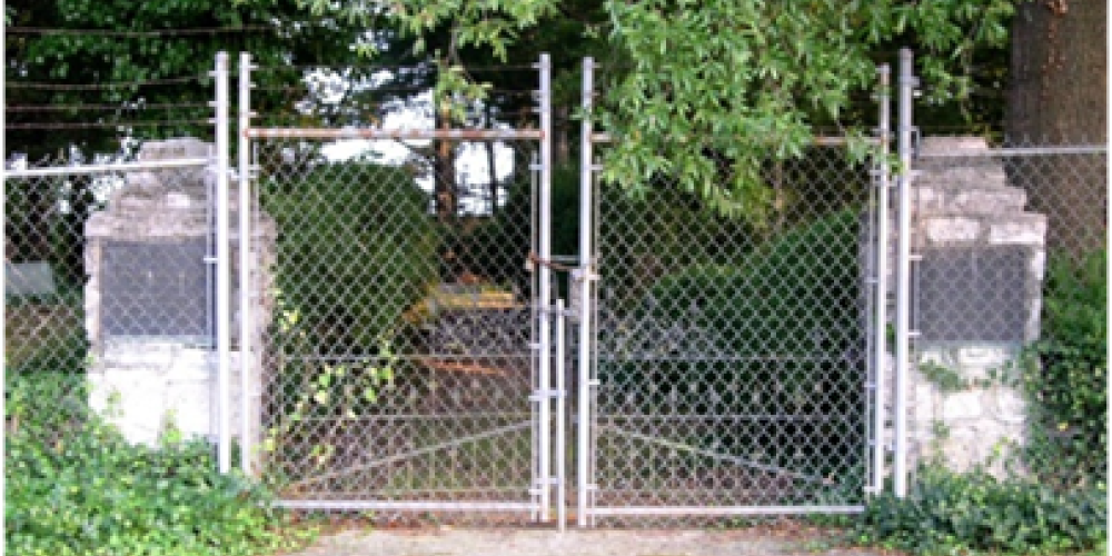 This wall stands two to three feet tall and features a double-door Colonial Revival-styled wrought iron gate entrance that is centrally located within the northwest wall. – Bettie Purcell