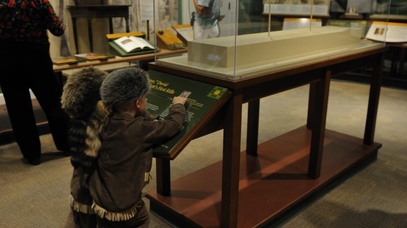 """Children are still drawn to the legends of Davy Crockett.  Two small Crockett """"wannabees"""" are entranced by Davy's first gun. – Dan MacDonald"""