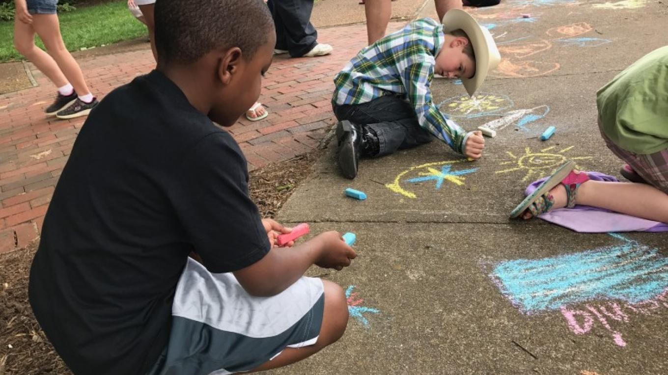 These young artists are enjoying the Chalk Crawl, sponsored by the Downtown Paris Association. – Susan Jones